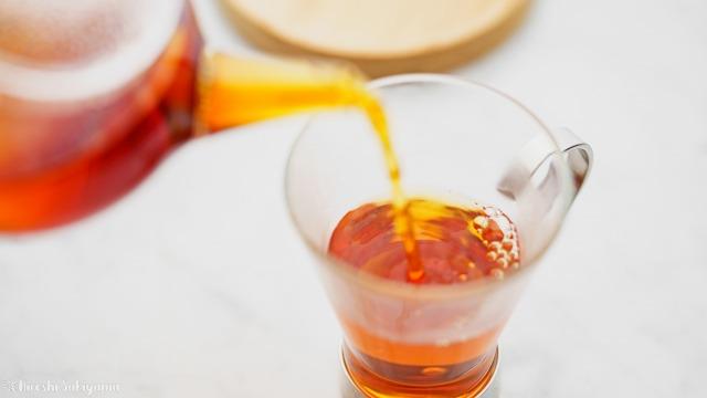 ティーポットからティーカップに紅茶を注ぐ