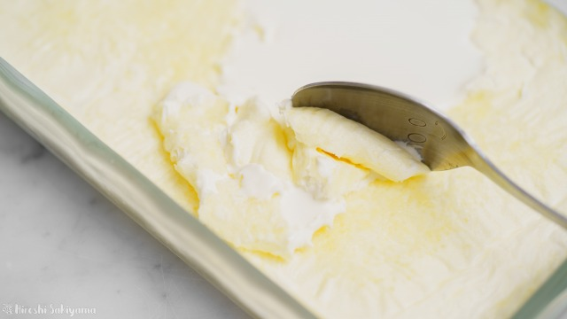 バットに出来上がったオーブンで作る自家製クロテッドクリームをスプーンですくった